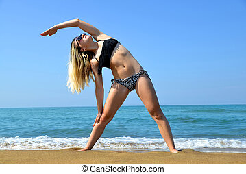 Young woman stretching body on sandy beach