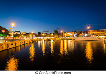 Buildings and boats along the waterfront at night, in...