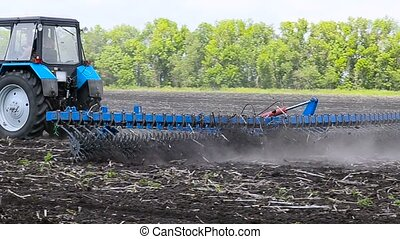 Tractor plow land. - Tractor with double wheeled ditcher...