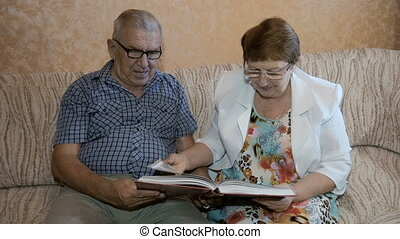 Beautiful couple in age, reading a book sitting on the couch at home.