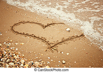 Heart on sand - Handwritten heart on sand with wave...