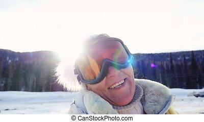 Happy adult woman smiles against mountains in winter in slow motion on the sun background. 1920x1080
