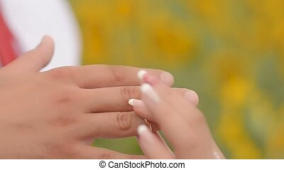 To dress a ring on a hand. - Woman to dress to the man a...