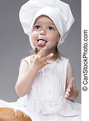 Portrait of Lovely Female Kid Posing as Cook. Tasting Food...