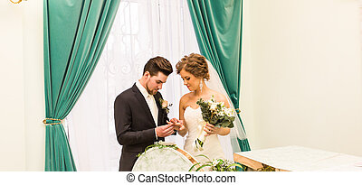 Groom puts the ring on the bride's hand in marriage registry...
