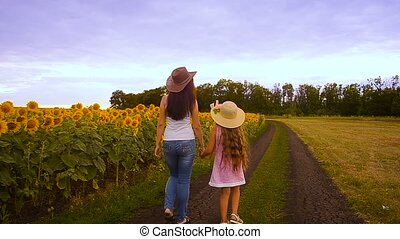 Mother and the daughter walk on the road, near the field of...