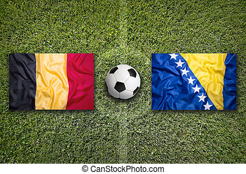 Belgium and Bosnia and Herzegovina flags on soccer field -...
