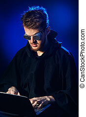 law violation - A hacker hiding his face behind glasses and...