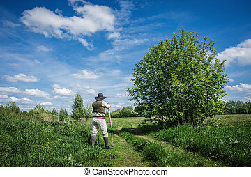 traveler in old clothes with a knapsack  on a country road