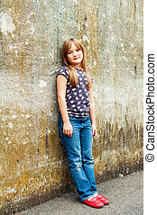 Outdoor vertical portrait of a cute little 7 year old girl wearing bright red shoes and denim jeans