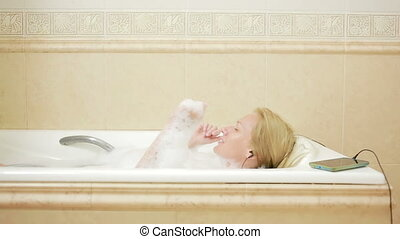 beautiful woman taking a bath and listening to music on...