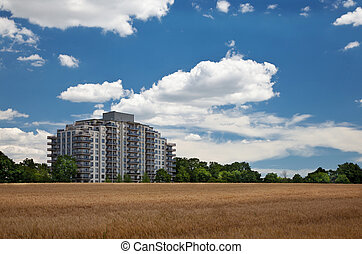 Modern residential high rise building in the middle of grain field landscape