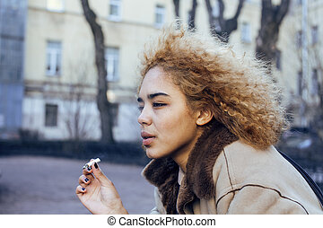 young pretty girl teenage outside smoking cigarette, looking...
