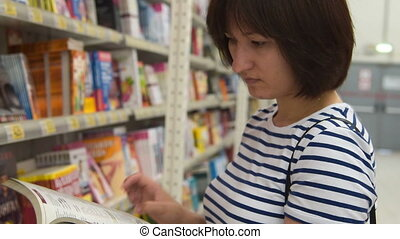 Woman looking through cookery book in the shop - Young woman...