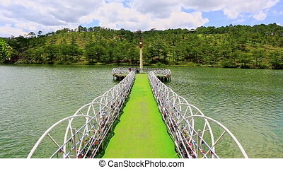 Narrow Lacy Bridge to Lighthouse in Lake Middle against Hill...
