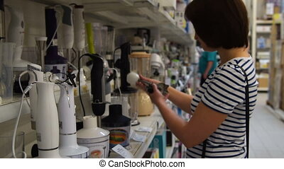 Woman choosing blender in the store - Young woman choosing...