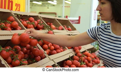 Woman choosing vine tomatoes in the grocery - Young woman...
