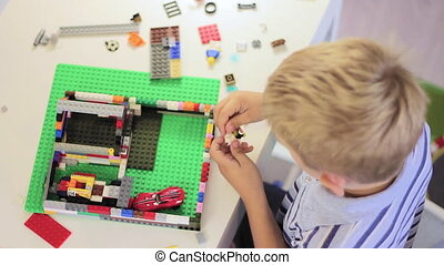 Child playing with a construction toy set, smart kid,...