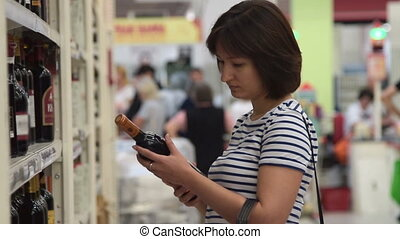 Woman buying red wine in the shop - Young woman in the...