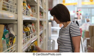 Woman buying food in the grocery - Young woman shopping for...