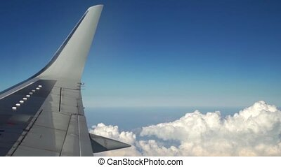 Airplane is flying in the blue sky through the white clouds. View of the airplane wing from the window. Traveling and transportation concept.