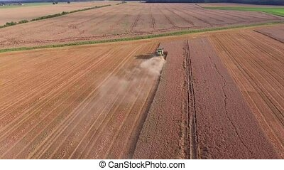 harvester working in the fields top down view