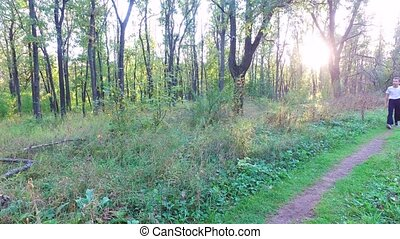 Slim teen boy goes along a path in the forest. The boy...