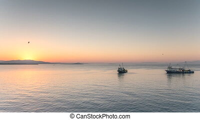Fishing trawler and boats crossing the sea in the morning before the sunrise. 4k