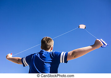 Flying Kite - Child flying a kite in the clear blue sky