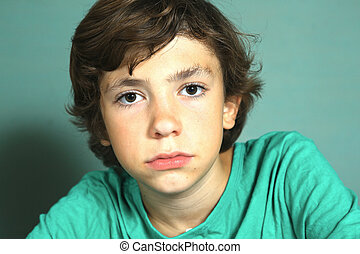 preteen handsome boy close up portrait on blue wall...