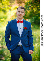 The groom in a blue suit with red butterfly and...