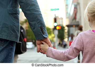 father holding the daughter child hand behind the traffic...