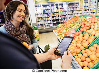Customer Using Digital Tablet With Woman In Grocery Store