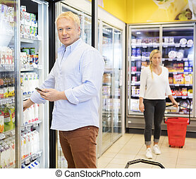 Man Holding Mobile Phone While Choosing Juices In Grocery...