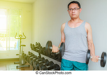 Training in the gym - Asia man middle aged training dumbbell...