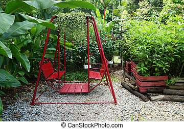 Red swing hanging in garden, in Hort Park, Singapore