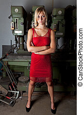 blonde in a red dress in a garage workshop