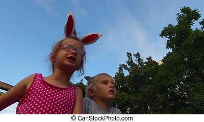 Girl with ears and glasses and boy with white hair fun talking on the background of blue sky.