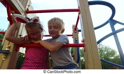 Girl with ears and glasses and boy with white hair having fun on the children's tower.