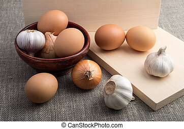 Still-life on the gray sacking - raw eggs, onions and garlic...