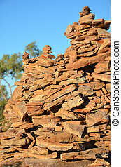 Close up of rock cairns, man made stone stacks, under blue...