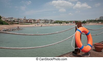 Wooden pier with orange life ring near the town's beach, 4k....