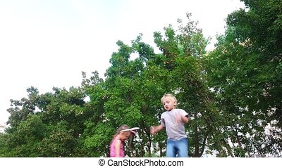 Boy child with white hair makes jumps. Girl with glasses and with the ears jumping behind boy