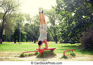 young man exercising on bench at summer park - fitness,...