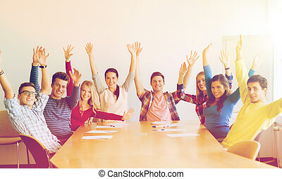 group of smiling students raising hands in office -...
