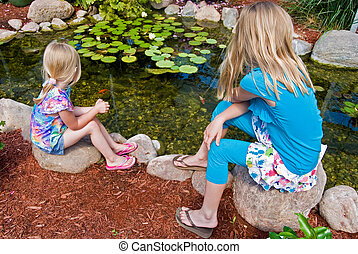 Koi Pond - Little girls watching Koi fish in pond