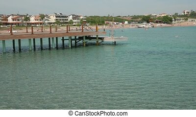 Scene of sunny day with empty wooden pier with resort town...