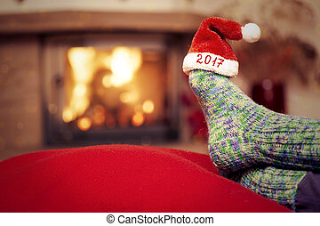 New year 2017 background with fireplace. - Feet in woollen...