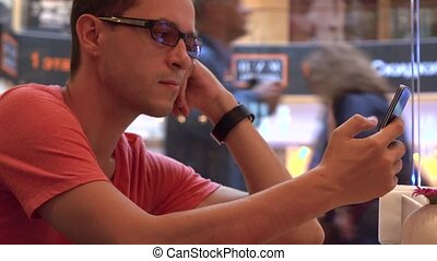 Bored hipster in black rim glasses tapping his mobile phones...