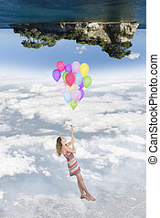 Hanging girl to a group of balloons flying toward a world...